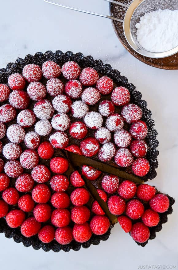 Top-down view of Easy No-Bake Chocolate Tart with Raspberries half dusted with powdered sugar