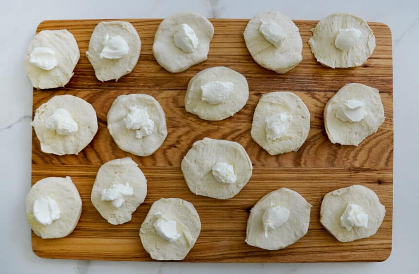 Top-down view of a wood cutting board with biscuits containing a dollop of cream cheese