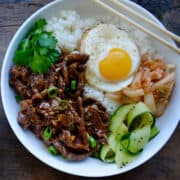 Easy Beef Bulgogi in a bowl with white rice topped with a fried egg, pickled cucumber, kimchi and fresh cilantro