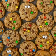 Top-down view of monster cookies studded with mini M&Ms and candy eyes