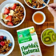 A top-down view of a carton of Florida's Natural Orange Juice next to granola parfaits with fruit and yogurt next to small bowls containing blueberries, honey and slices of kiwi.