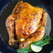 Simple Roast Chicken with Garlic and Lemon in a cast iron skillet with fresh rosemary