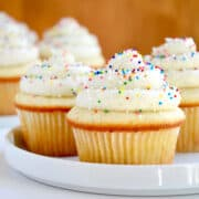 Vanilla bean cupcakes topped with vanilla bean buttercream frosting and rainbow sprinkles