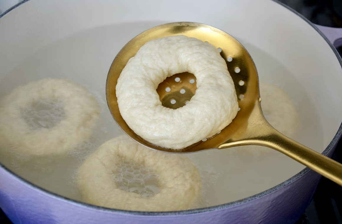 A soft pretzel bagel being dipped in a baking soda bath