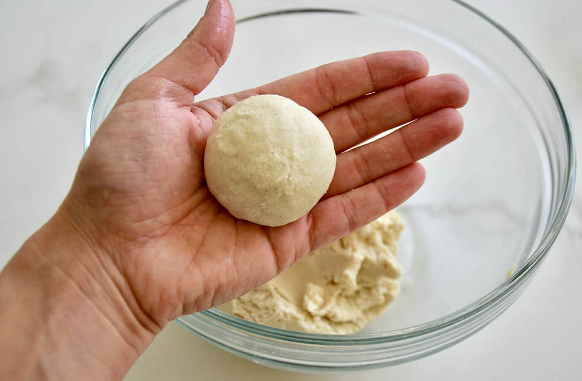 A hand holding corn tortilla dough shaped into a ball