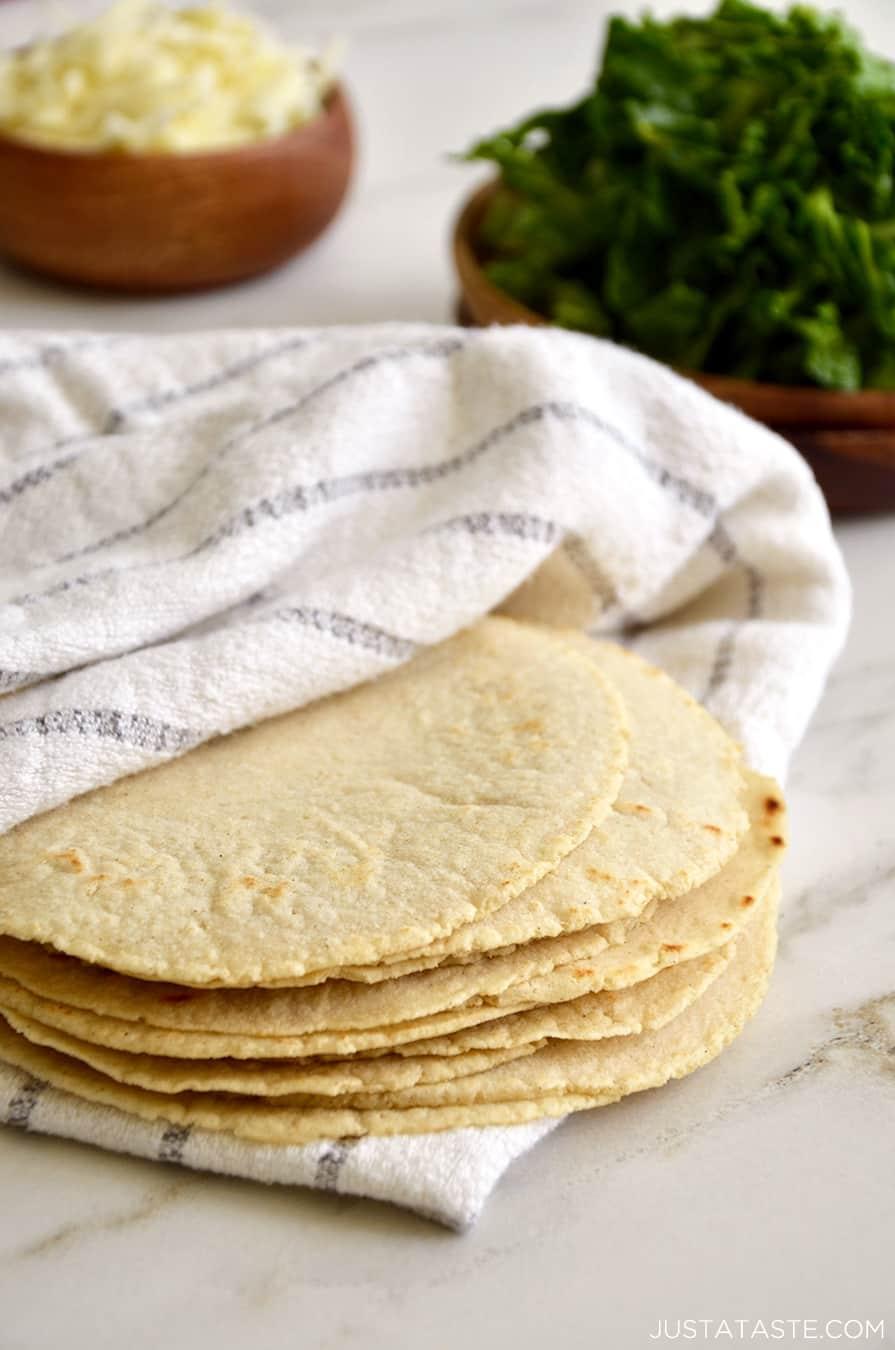 A stack of homemade corn tortillas inside a towel