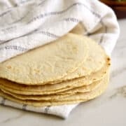 Stack of freshly made homemade corn tortillas wrapped in a white dish cloth.
