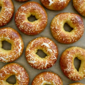 A top-down view of Easy Soft Pretzel Bagels on tan parchment paper