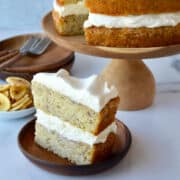 A slice of banana cake topped with cream cheese frosting on a plate with the rest of the cake on a cake stand in the background.