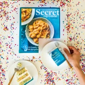 The Secret Ingredient Cookbook as a cake surrounded by rainbow sprinkles