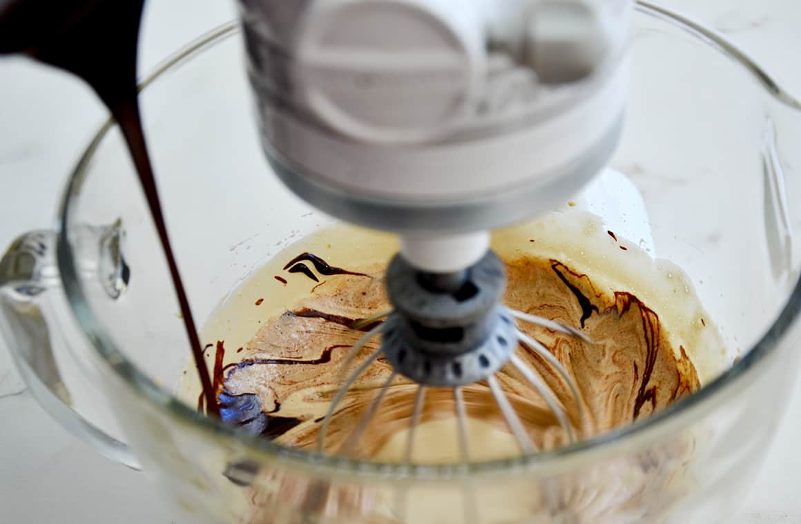 A stand mixer with the whisk attachment and chocolate being poured in