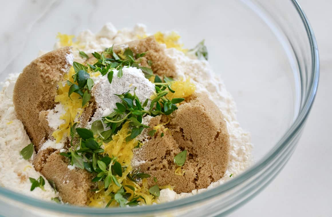 A glass bowl containing brown sugar, flour, thyme and lemon zest