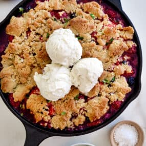 A cast-iron skillet with fruit crumble topped with ice cream