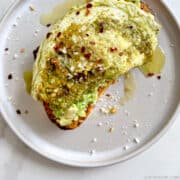 Top-down view of a Pesto Egg atop toasted bread with avocado garnished with crushed red pepper flakes and grated parmesan cheese.
