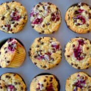 """Top-down view of Raspberry Chocolate Chip Muffins in a muffin pan with text underneath that reads, """"Raspberry Chocolate Chip Muffins"""" and the purple Just a Taste logo."""