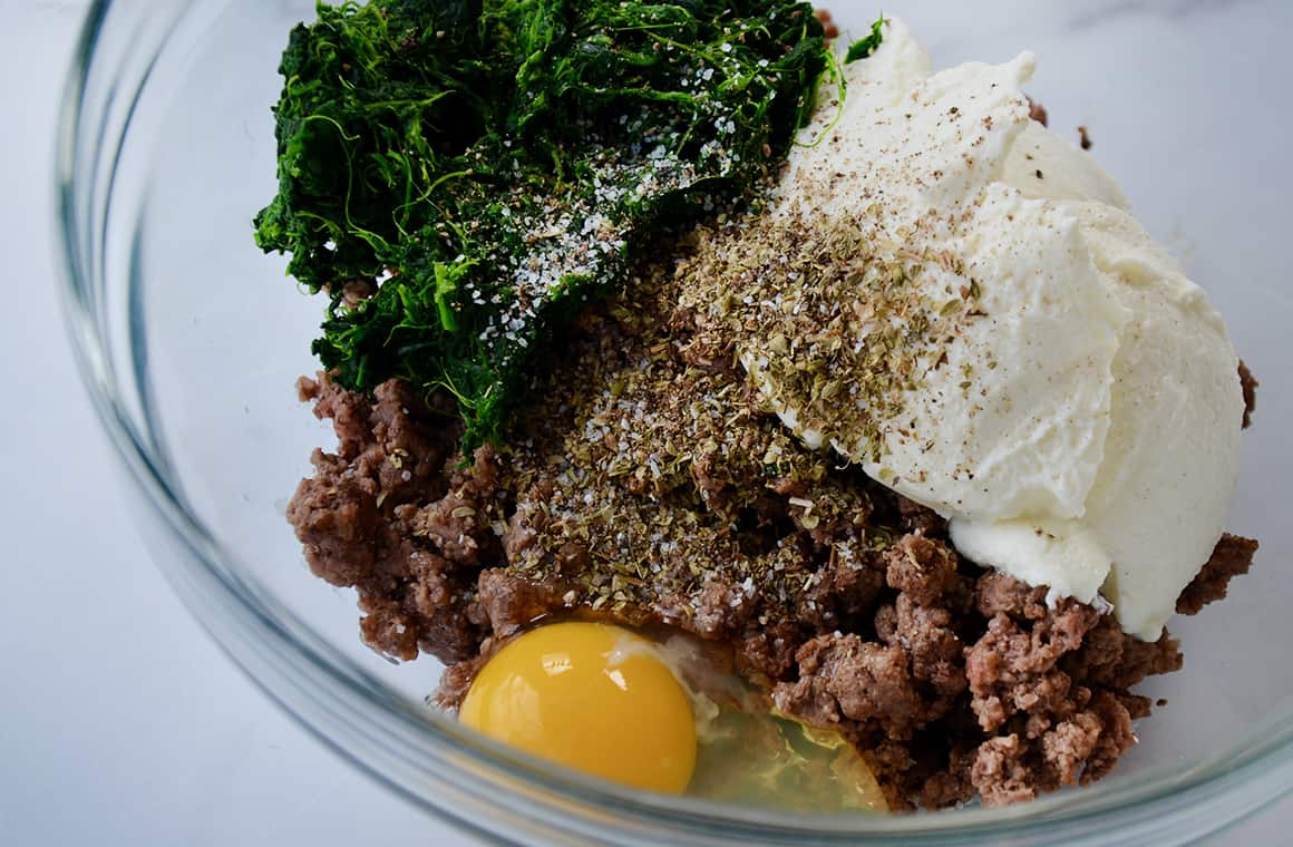 A glass bowl containing ground beef, ricotta, spinach and eggs