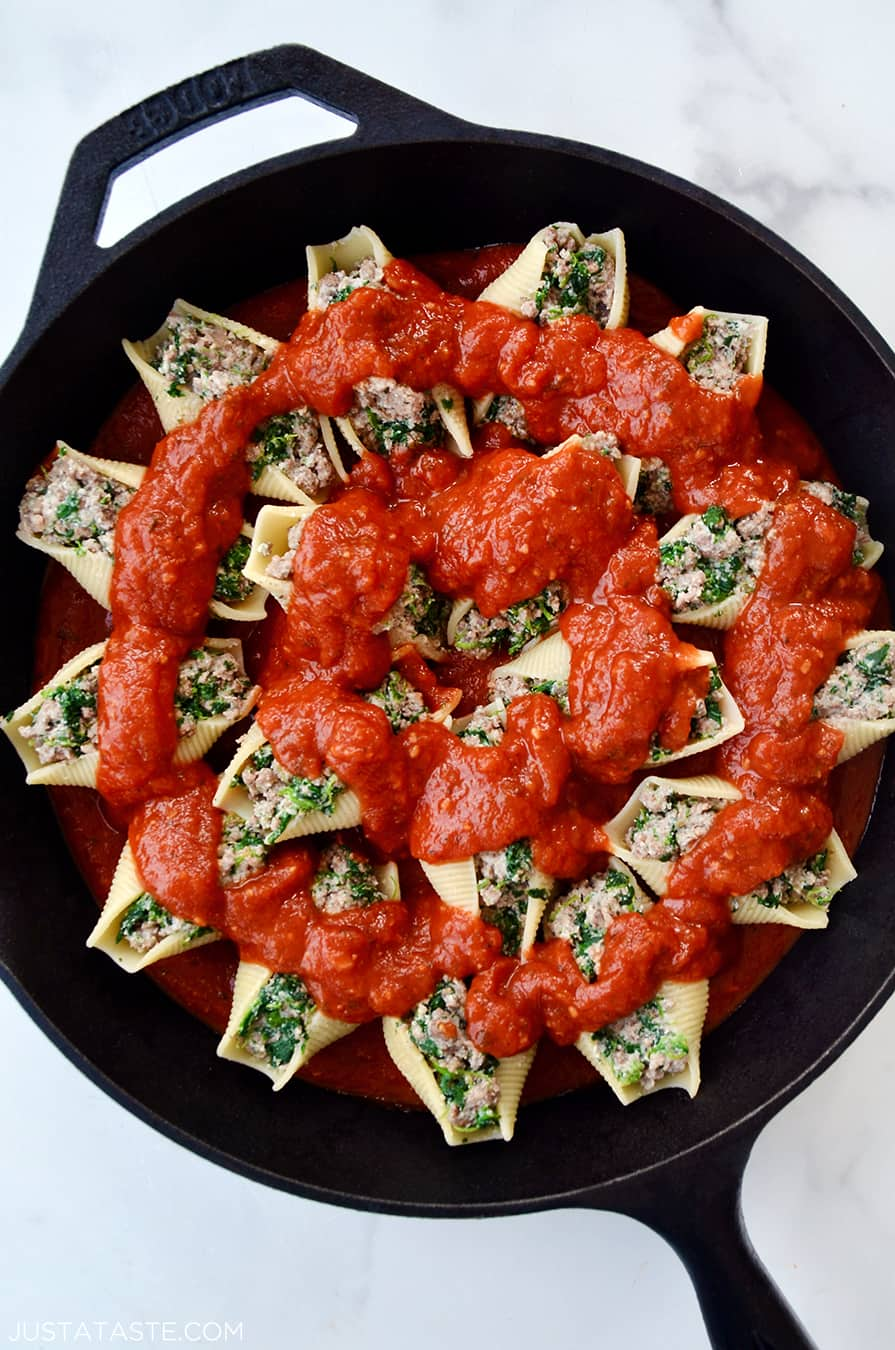 A cast-iron skillet with stuffed shells and tomato sauce on top