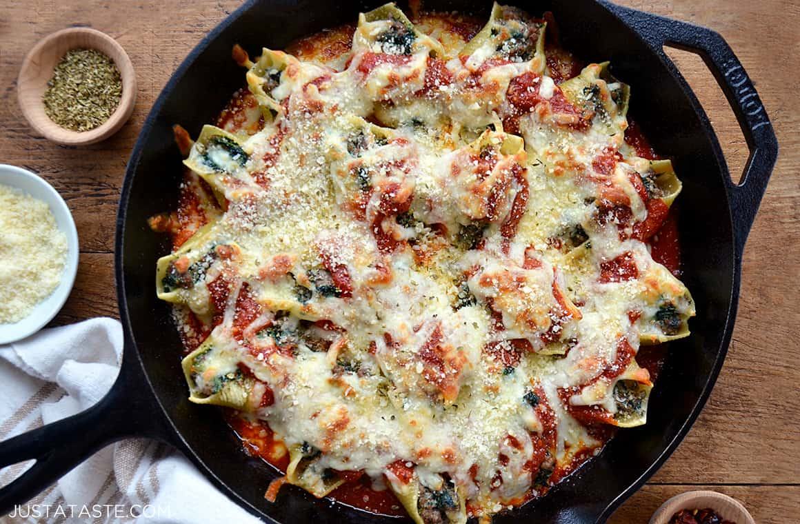 A cast-iron skillet containing stuffed shells with meat and ricotta