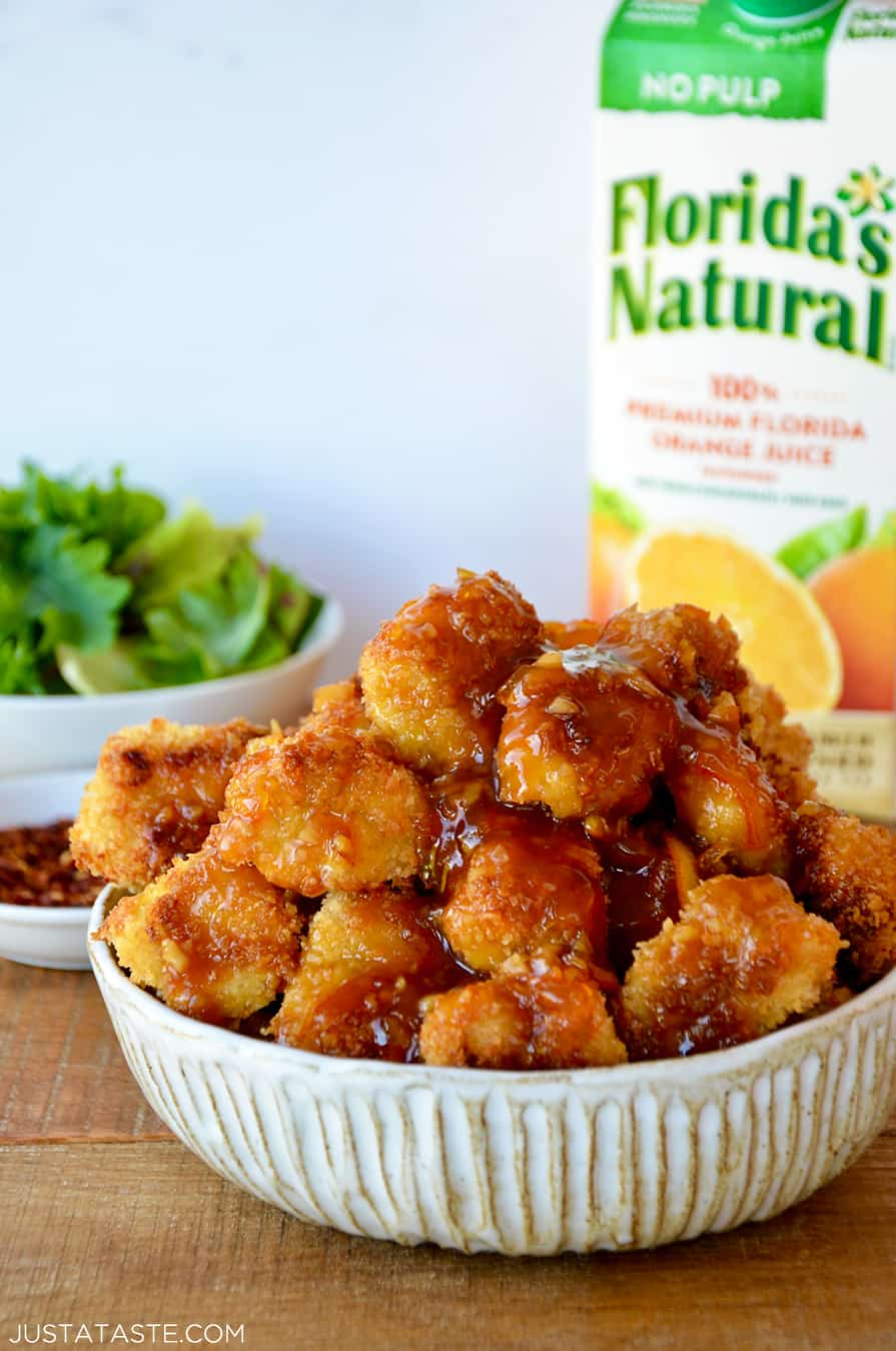 A white bowl containing baked orange chicken with a carton of Florida's Natural Orange Juice in the background