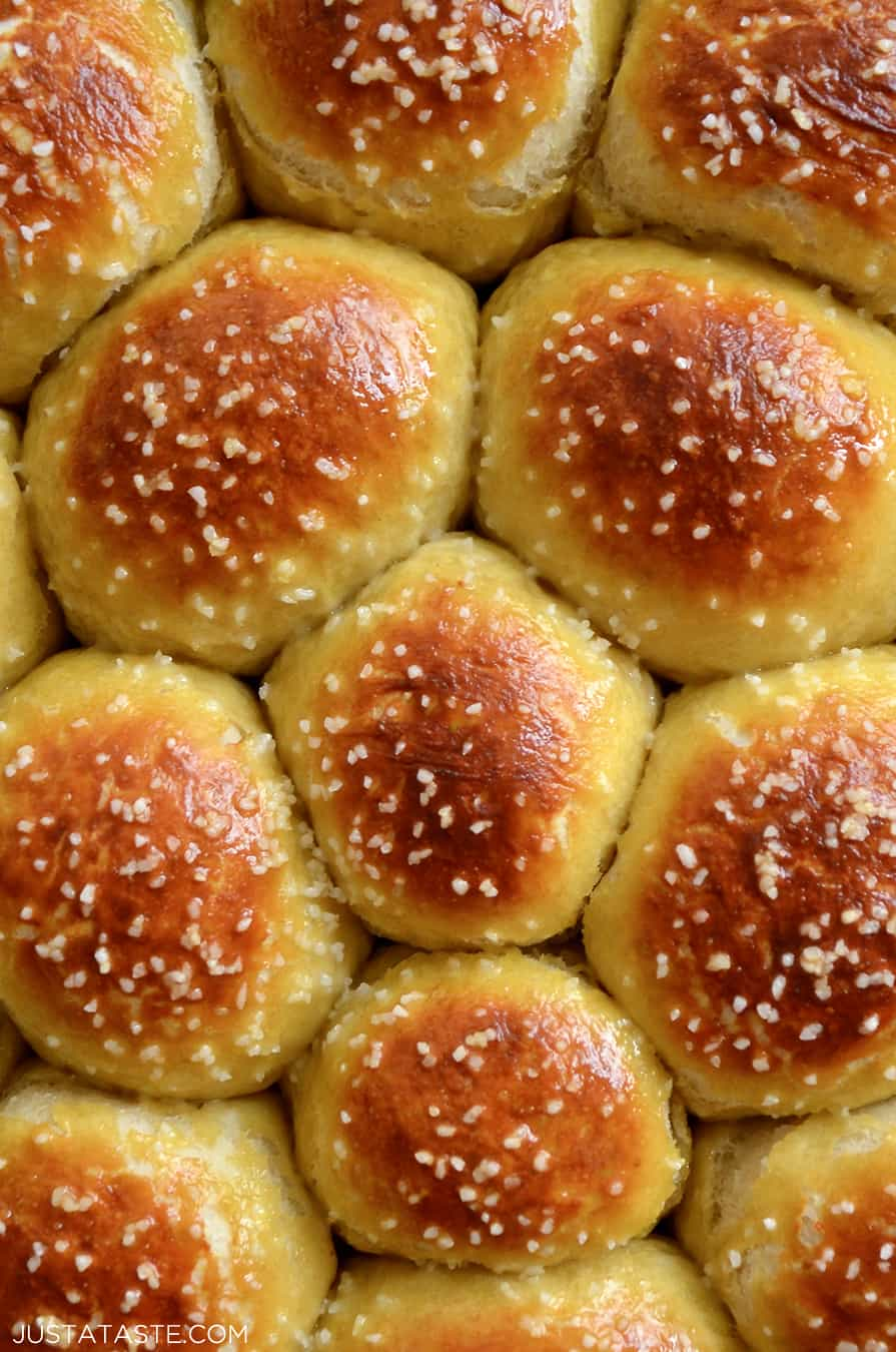 A close-up of baked pretzel rolls topped with salt