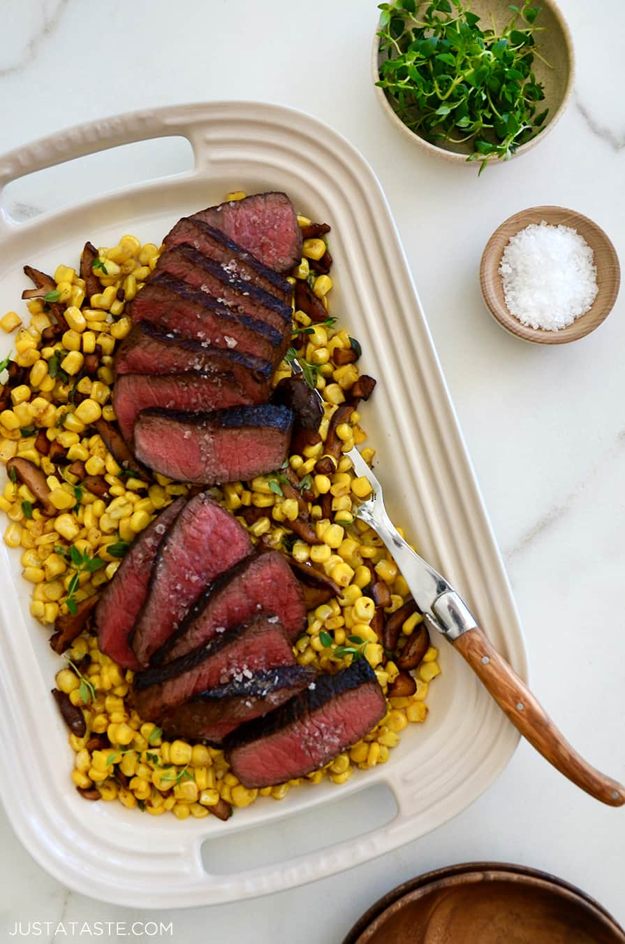 A white platter containing steak and corn with thyme