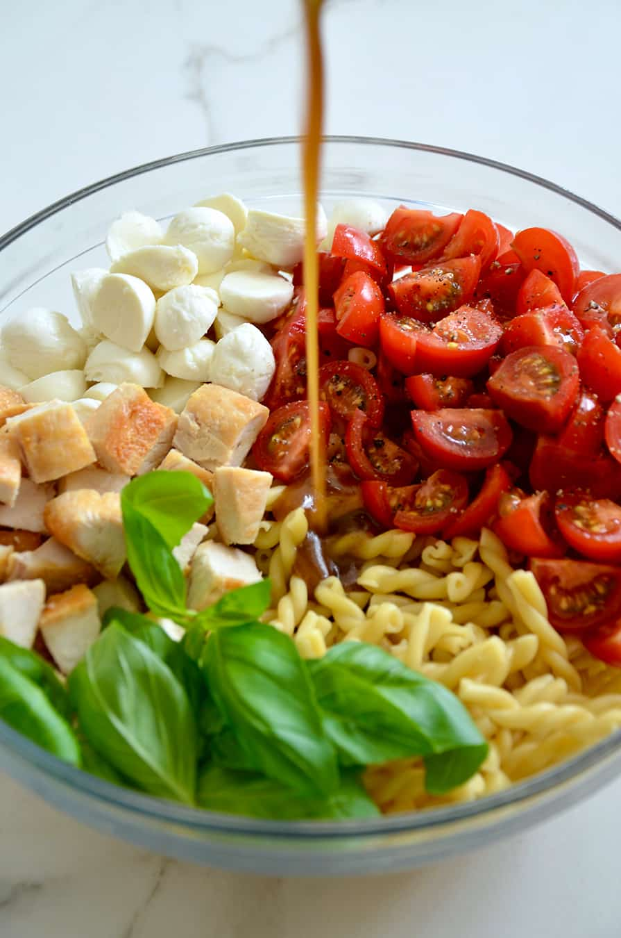 A glass bowl containing pasta, basil, mozzarella and tomatoes with dressing being poured in