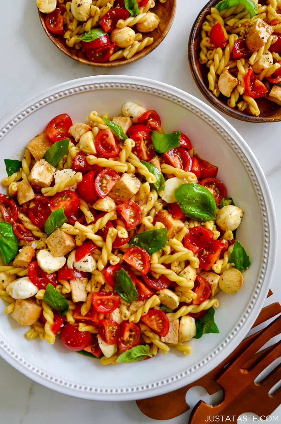 A white bowl containing pasta salad with tomatoes and basil
