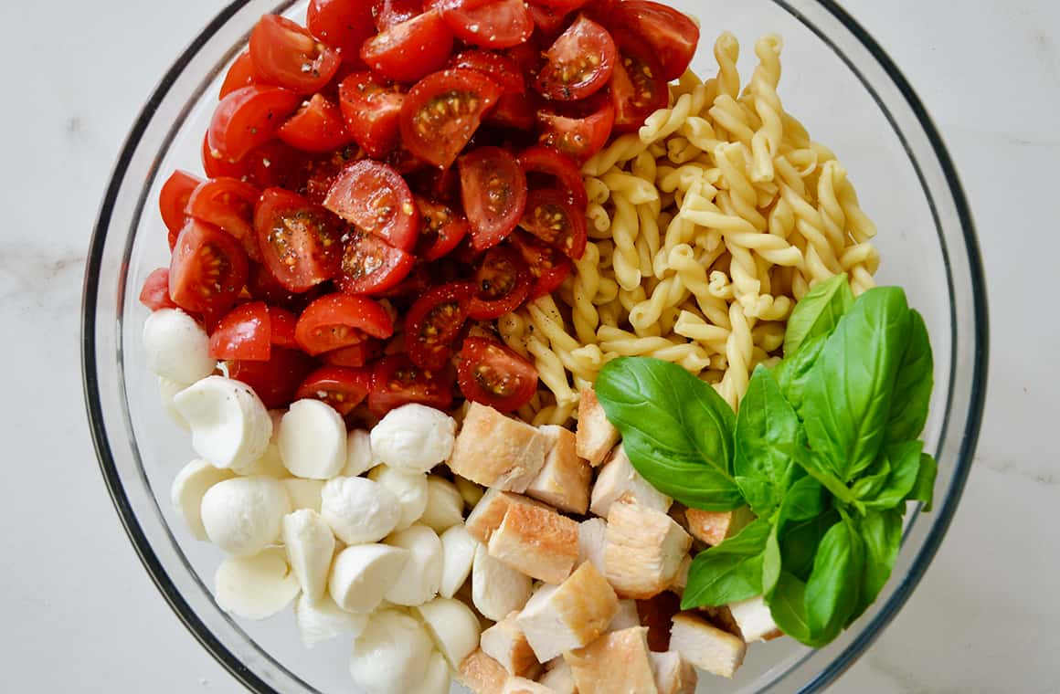 A glass bowl containing tomatoes, pasta, basil, chicken and mozzarella