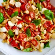 A large white bowl containing pasta salad with chicken, mini mozzarella balls, cherry tomatoes and fresh basil.