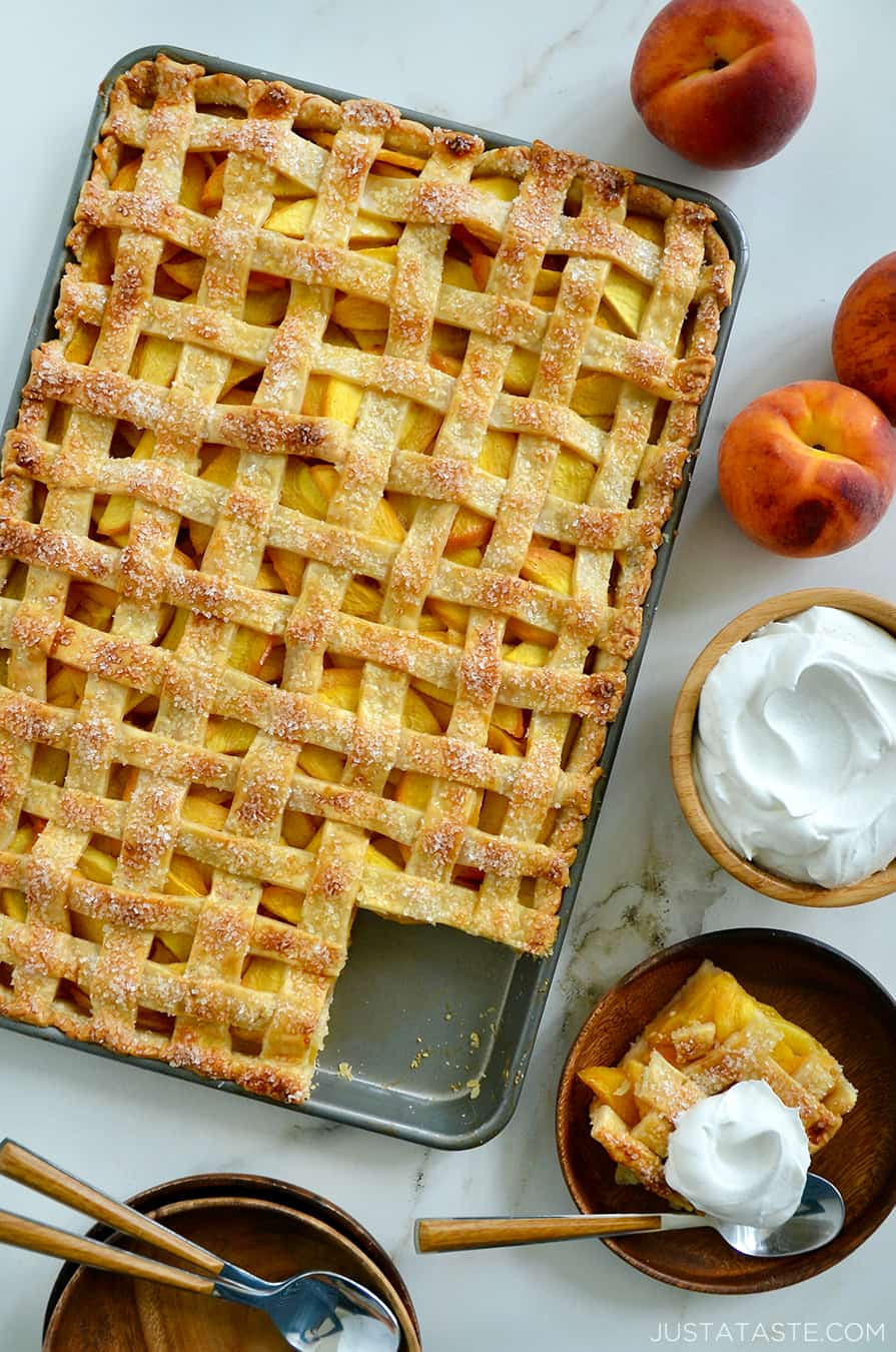 A slab pie surrounded by whipped cream and peaches