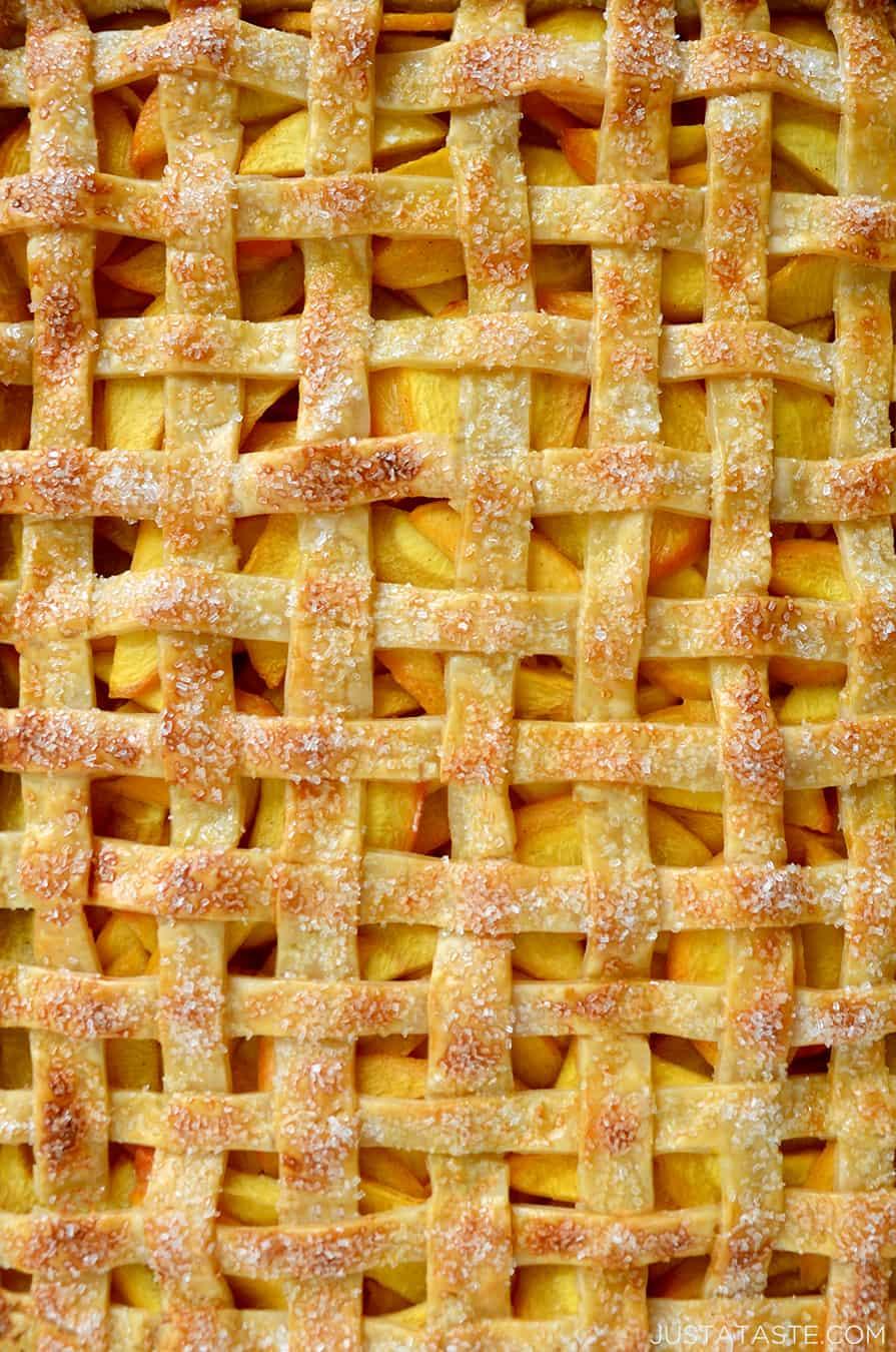 A close-up of lattice pie crust with peach filling