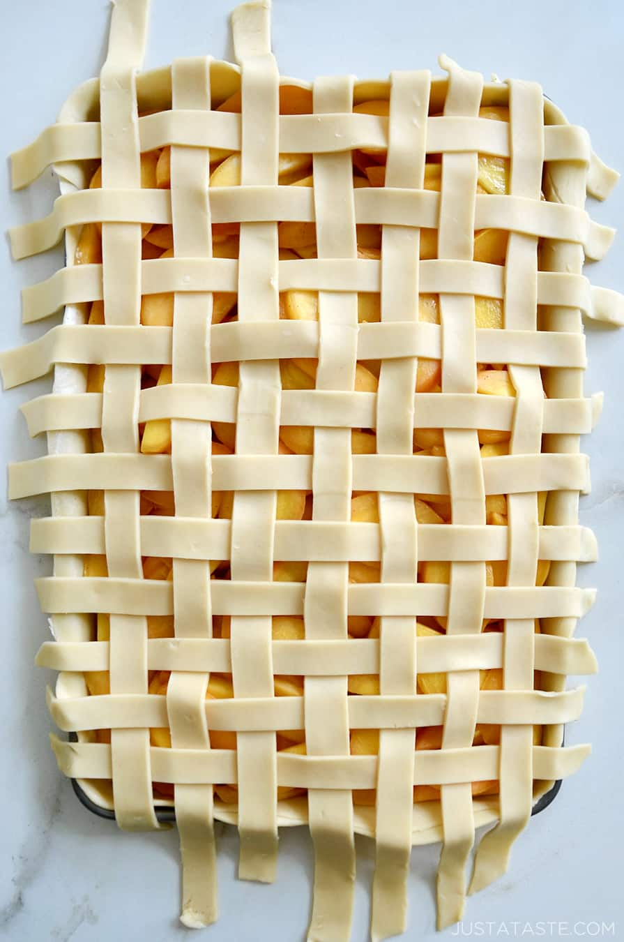 A top-down view of lattice pie crust on a peach slab pie
