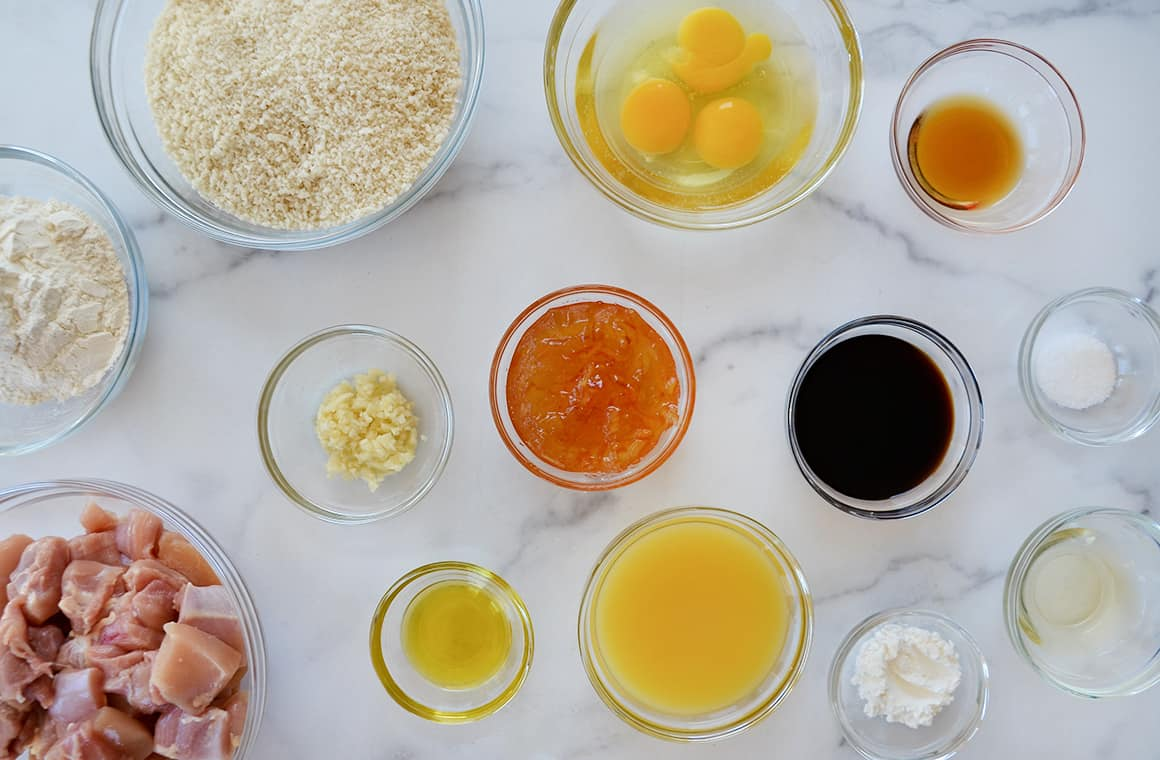 Glass bowls containing ingredients, including chicken thighs, orange juice and soy sauce