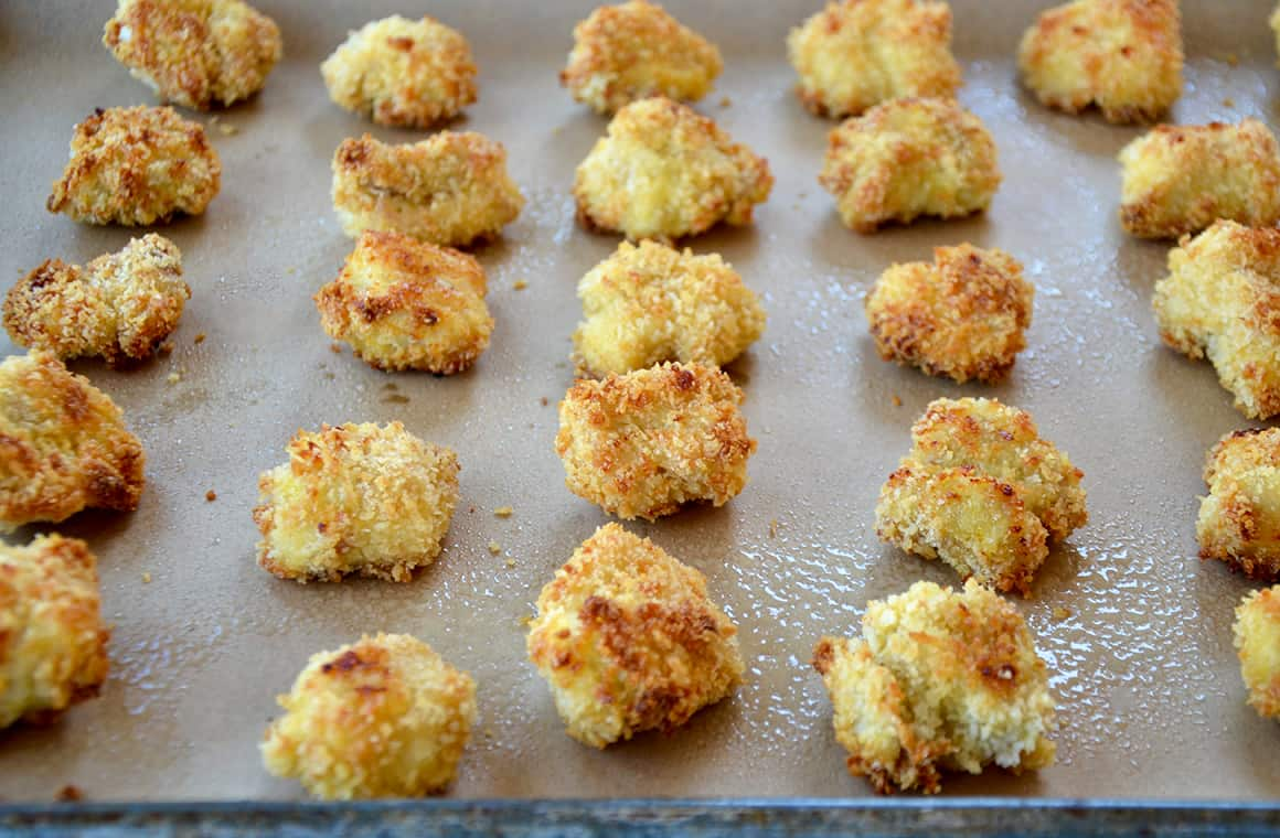 Homemade Panko chicken nuggets lined up on a baking sheet