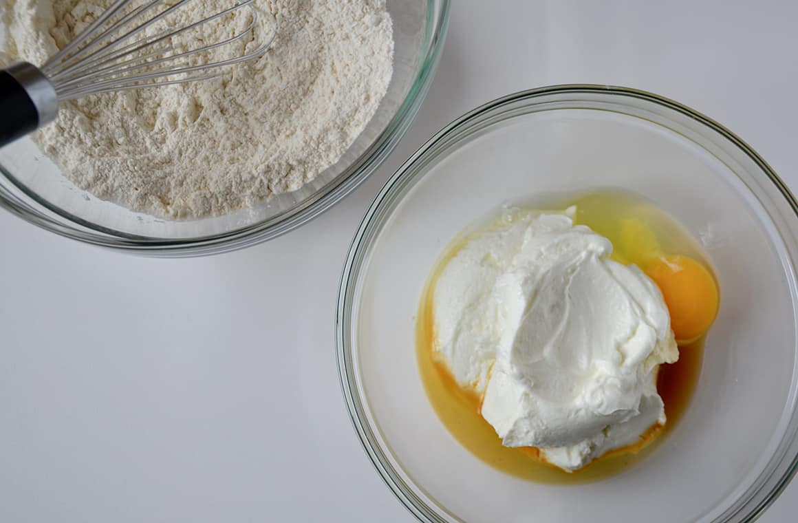 Two glass bowls containing wet and dry ingredients for pancakes