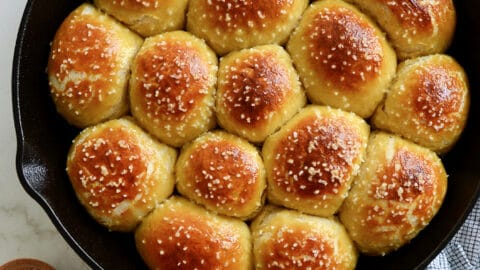 A cast-iron skillet filled with pretzel rolls with a small bowl of salt