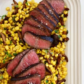 A white platter with corn, mushrooms and sliced steak