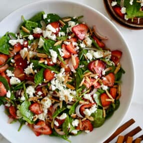 A top down view of a white bowl containing Spinach Strawberry Salad with Poppy Seed Dressing