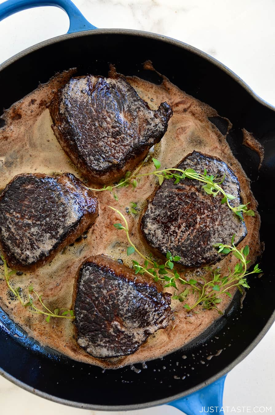 A blue skillet containing steaks with thyme and butter