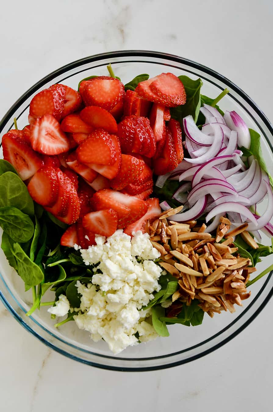A glass bowl containing spinach, strawberries, onions, nuts and feta cheese