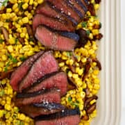 Top-down view of sliced steak sprinkled with sea salt over a bed of corn and mushrooms.