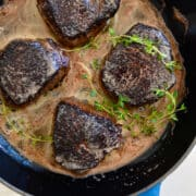 Four cooked steaks with fresh thyme in a skillet.