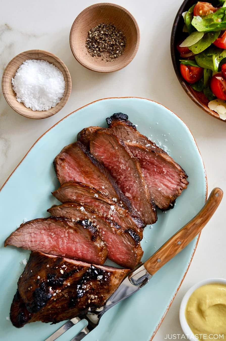 Sliced tri-tip on a blue serving platter with salt and pepper
