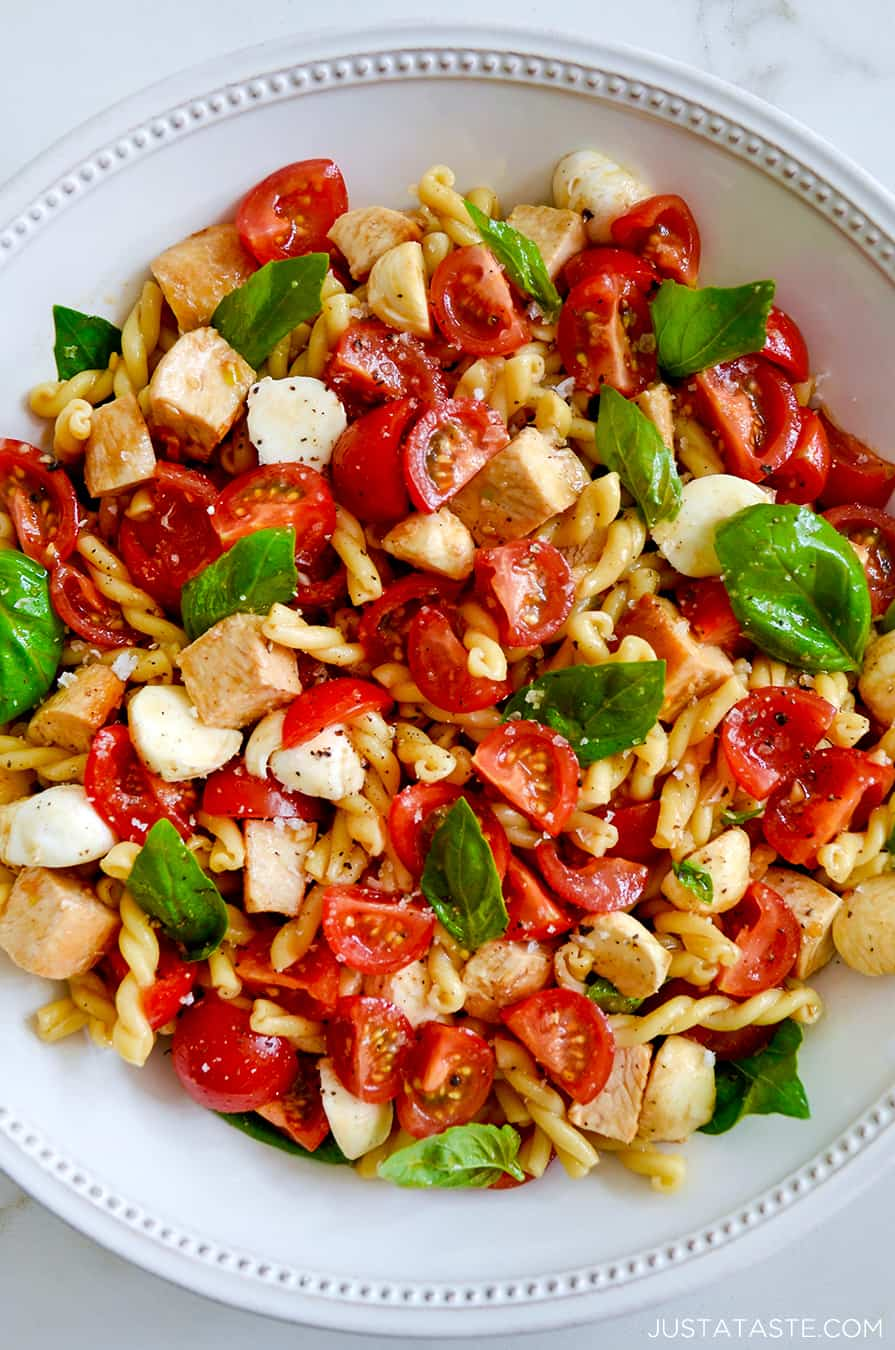 A large white bowl containing pasta salad with tomatoes and basil