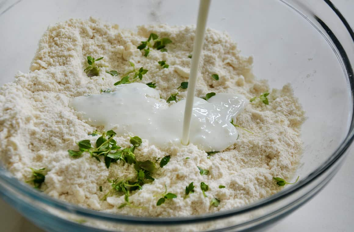 Buttermilk being poured into biscuit dough with thyme
