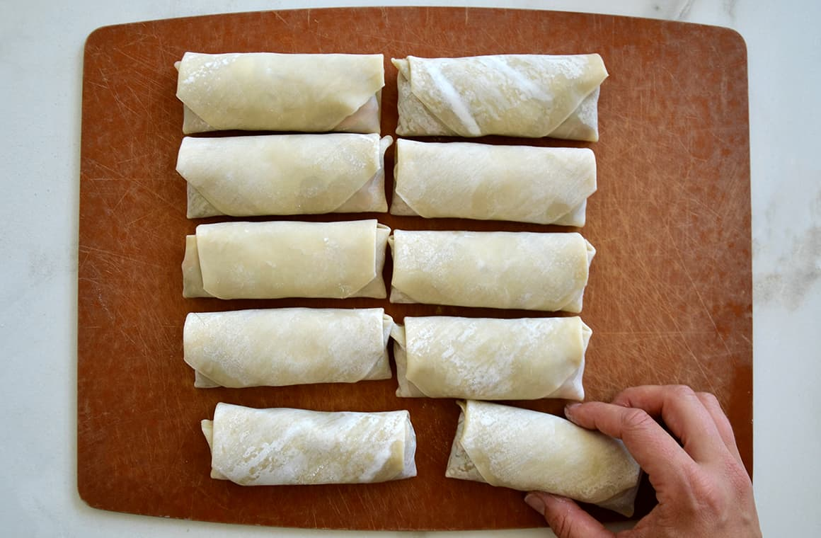 Two rows of formed egg rolls with a hand reaching for one of them