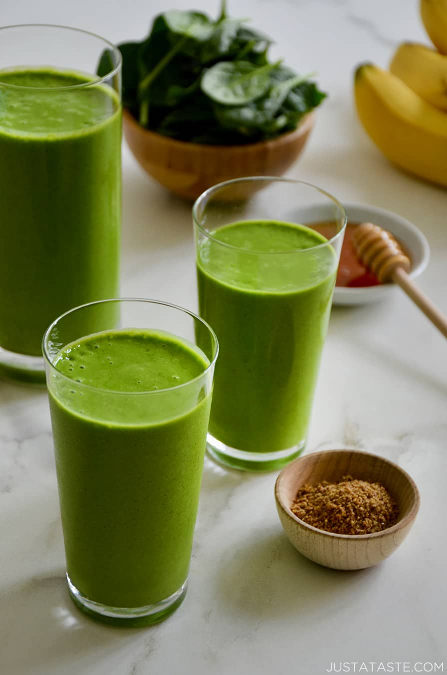 Three glasses filled with Healthy Green Smoothies next to a bowl containing fresh spinach, a small bowl filled with honey and another small bowl containing ground flaxseed.