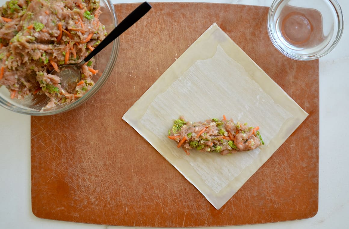 Ground chicken mixture atop a single egg roll wrapper next to a bowl containing a spoon and ground chicken mixture