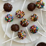 No-Bake Chocolate Cookie Pops decorated with rainbow and chocolate sprinkles on a white plate next to small bowls containing rainbow sprinkles.