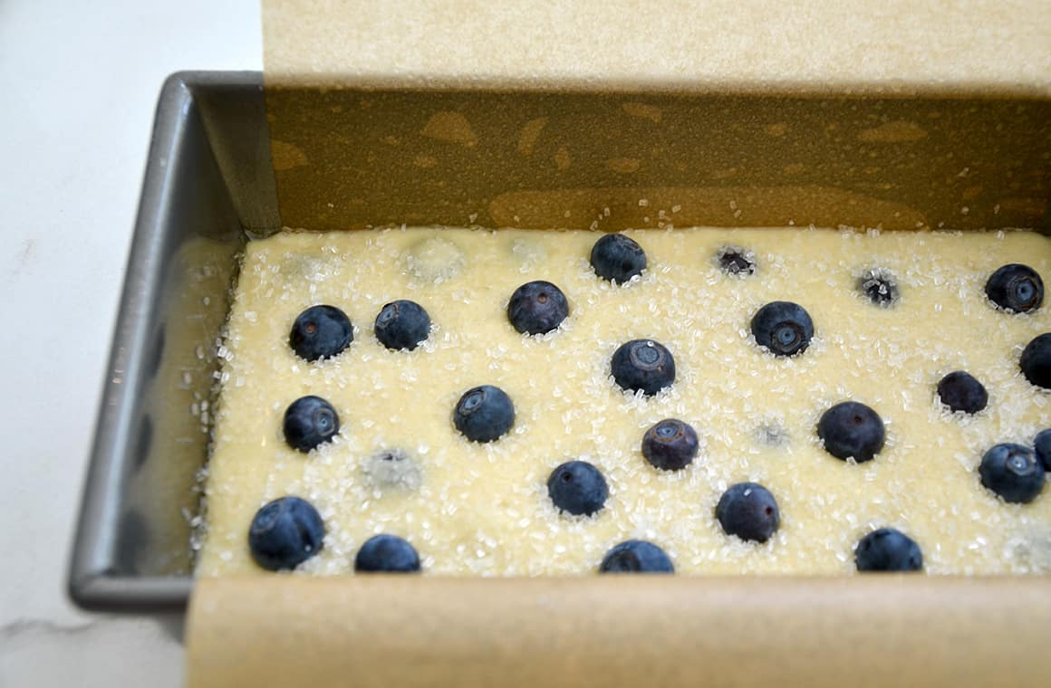 A loaf pan lined with parchment paper containing bread batter, blueberries and sanding sugar
